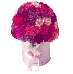 Caja cilíndrica rosada con claveles lila rosado. Morado y fucsia